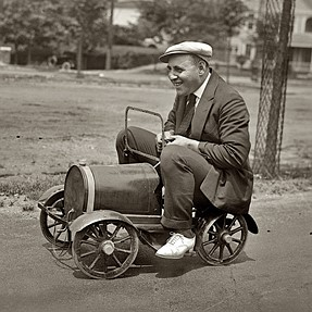 Photo of a man driving a tiny car from 1920 for play